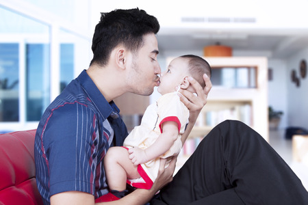 Portrait of young father kissing his adorable baby boy while sitting on the sofa