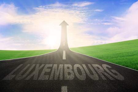word: Image of empty highway with word of Luxembourg and arrow upward at the end of a road