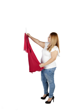 Full length of a young overweight woman holding a red dress to try in the studio, isolated on white background Stock Photo