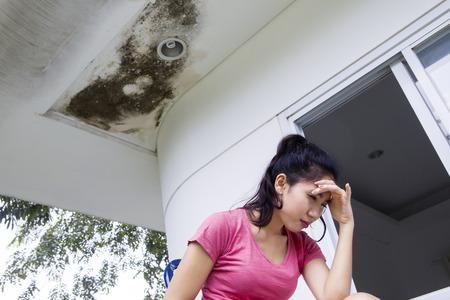 손상된 천장 아래 앉아있는 동안 아시아 여자의 이미지 스트레스가 보입니다. 스톡 콘텐츠