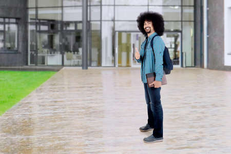 Full length of a male Afro student standing at school yard while showing thumb up and holding books