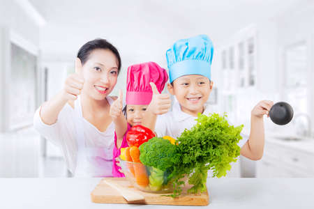 Happy Asian family showing thumbs up in the kitchen with a bowl of vegetables on the table photo