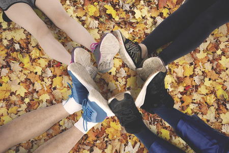 Top view of friends make foot circle with their legs and different shoes on autumn leaves at the park Stock Photo