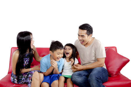 Young parents sitting on the couch with their children while laughing together, isolated on white background photo