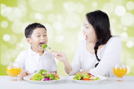 Portrait of beautiful mother feeding her son with fresh salad. Shot with bokeh background photo