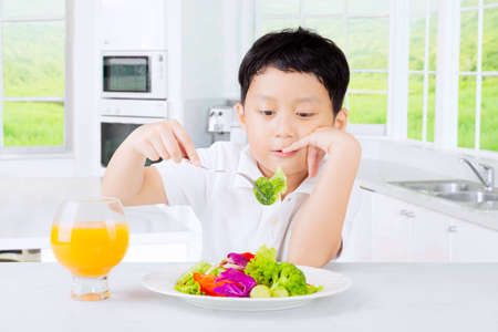 Cute boy tasting a plate vegetables salad and looks bored, shot in the kitchen at home photo