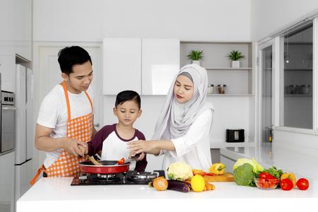 부엌에서 음식을 준비하면서 함께 요리하는 이슬람 가족의 사진