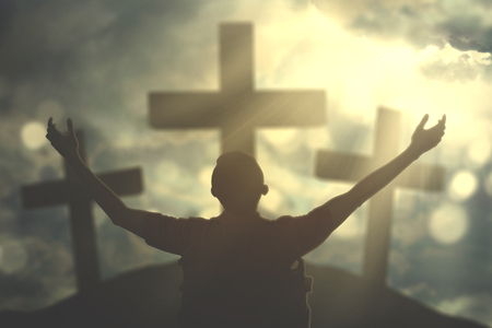Image of disabled man raising hands while praising and praying to god with three crucifixes under sunrise