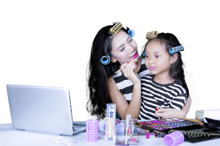 Image of Asian mother helping her daughter to doing makeup while using a computer laptop photo