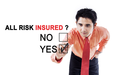 Image of young businessman using a pen while choosing a yes option on the whiteboard with text of all risk insured photo