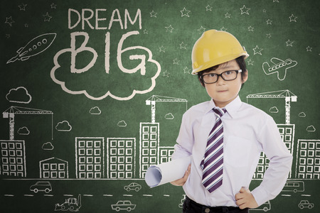 Cute little engineer holding a blueprint while standing with text of dream big and scribbles on the chalkboard photo