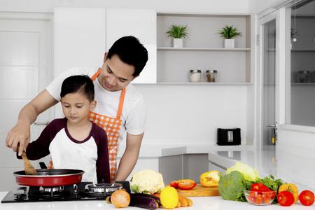 Beeld van jonge vader die zijn zoon onderwijzen aan het koken terwijl het voorbereiden van voedsel in de keuken