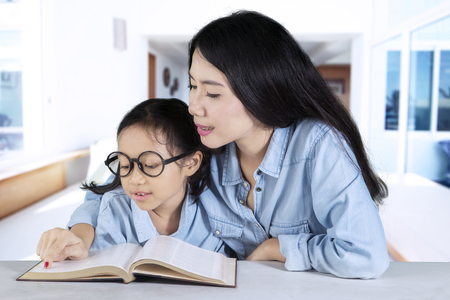 Photo of a young Asian mother teaching her daughter to read a book at home photo
