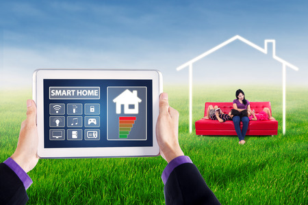 Applications of smart house controller on the tablet screen with young woman and her children using gadget on sofa at field under a house symbol photo