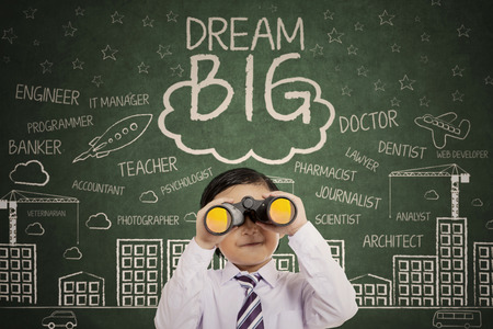 Cute boy looking through binocular standing with a text of dream big and scribbles on the chalkboard photo
