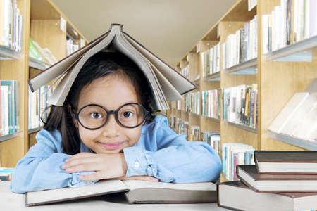 Image of adorable girl studying with books in the library while sitting with a book over her head photo
