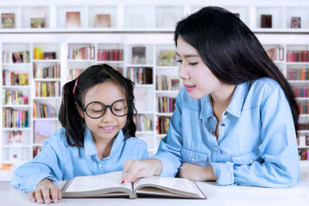 Picture of pretty teacher guides her student to reading a book while sitting in the library photo
