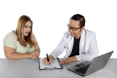 Portrait d'un médecin masculin en train d'écrire une ordonnance pour une femme en surpoids après un contrôle Banque d'images