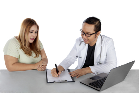 Portrait of a male doctor writing a prescription for an overweight woman after checkup photo