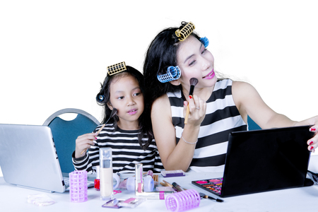 Image of young woman teaching her daughter to doing makeup, isolated on white background photo