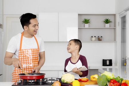 Young father cooking vegetable on the stove with frying while talking with his son in the kitchen Foto de archivo