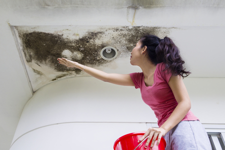 Picture of young woman collecting drop rainwater with her hand from damaged ceiling
