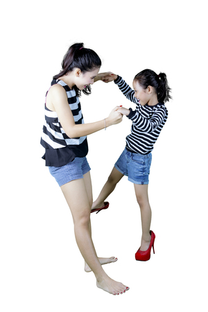 Portrait of young mother holding her daughter while playing with high heels shoes, isolated on white background Stock Photo