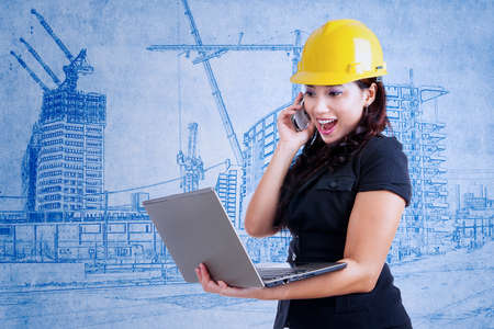Beautiful architect is laughing on the phone while holding laptop on blueprint background photo