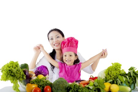 Image of mother and daughter looking at the camera and raising hands while sitting with vegetables, isolated on white background photo