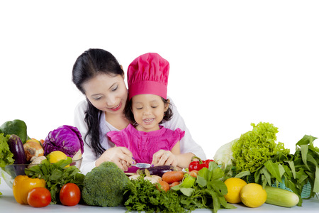 Picture of a beautiful mother teaching her cute chef to cook while cutting an eggplant, isolated on white background photo