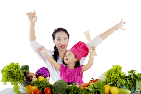 Picture of a cute girl and her mother raising hands together while sitting with vegetables in the studio photo