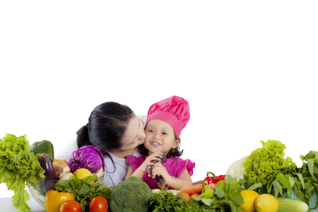 Image of little girl chef is kissed with her mother while preparing to cook in the studio photo