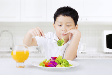 Portrait of a male kid sitting in the kitchen and looks dislike eat vegetables, shot at home