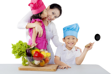 Image of young mother smiling at the camera while preparing for makes a salad with her children in the studio photo