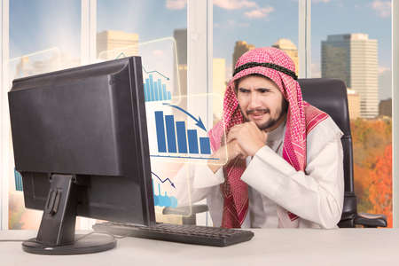 Portrait of middle eastern male entrepreneur is feeling confused while looking at a declining business graph on the monitor with autumn background on the window photo