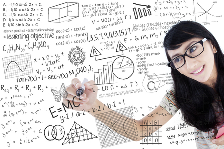 Portrait of Asian female college student using marker to write math formula on the whiteboard photo