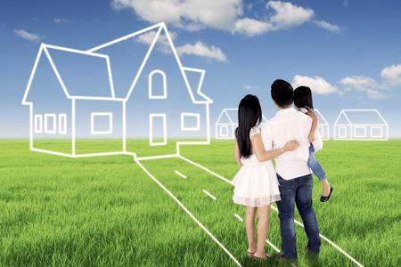 Achteraanzicht van een jonge familie omarmen elkaar terwijl ze naar hun droomhuis kijken