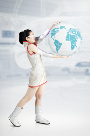 Portrait of a futuristic woman standing on the cyberspace while holding a virtual globe
