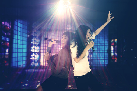 Two women having fun together in the night club while singing under a disco ball with bright rays