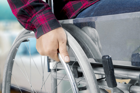 Close up of disabled mann hand holding a wheel while using a wheelchair Banco de Imagens