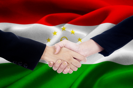 Image of two businesspeople hands closing a meeting by shaking hands in front of a national flag of Tajikistan