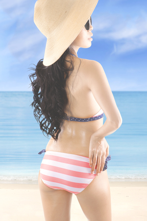 Summer Concept. Rear view of a young woman with beautiful body and long hair, posing at the coast while wearing a striped swimsuit, sunglasses, and straw hat.