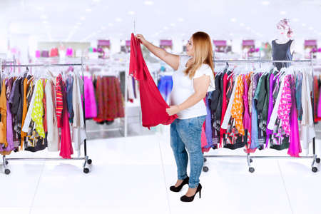 shirt hanger: Image of fat woman choosing a dress while standing in the clothing store Stock Photo