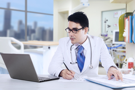 Portrait of male doctor is writing a prescription at the clinic