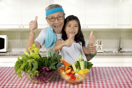 老人と孫娘テーブルの上の野菜のボウルとキッチンで親指を表示します。 写真素材 - 85331532