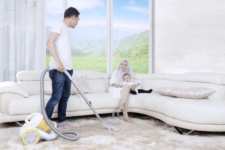 Young father cleaning carpet by using vacuum cleaner while his wife and child sitting on sofa with mountain background on the window