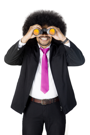 Portrait of Afro businessman smiling at the camera while looking through a binocular in the studio
