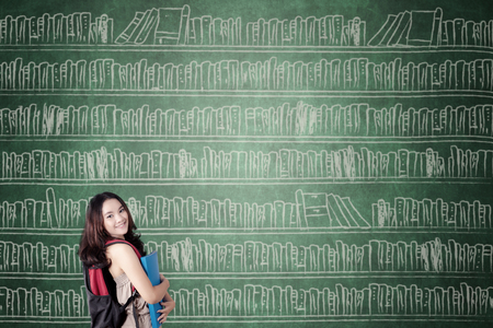 Female high school student smiling at the camera and carrying a folder while standing with books on the chalkboard