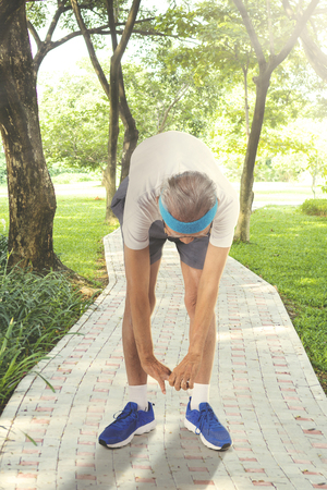 Picture of an elderly man wearing sportswear while doing a workout in the park