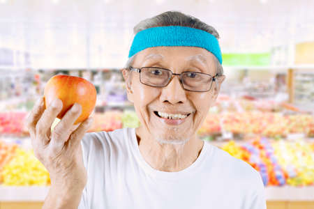 Old man looking at the camera while showing an organic apple in the supermarket
